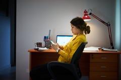 Студент девушки изучая на ноче печатает сообщение на телефоне Стоковые Изображения