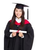 Студент девушки молодого студент-выпускника держа и показывая диплом Стоковое Изображение