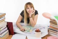 Студент девушки на столе засорянном с книгами и чертежами с улыбкой смотрит в рамке Стоковое Изображение