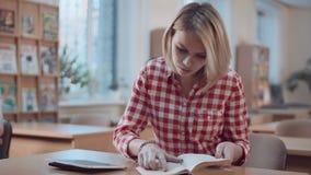 Студент девушки работая с книгой и таблеткой Стоковая Фотография RF