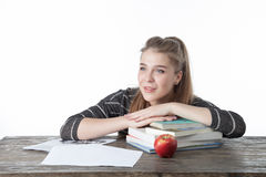 Студент девушки сидя на деревянной таблице с ее руками на книгах Усмехаясь девушка с яблоком, книгами, на деревянном столе Стоковая Фотография RF