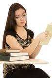 Студент девушки смотря кучу книг на ее столе Стоковое Фото