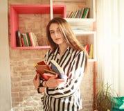 Студент девушки с книгами в библиотеке Стоковое Изображение