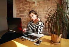 Студент девушки с компьтер-книжкой на таблице работая дома Стоковое фото RF