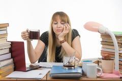 Студент девушки уныло и сонно читающ его проект тезиса сидя с чашкой кофе в руке стоковая фотография rf