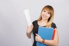 Студент девушки усмехаясь и держа светокопии и папку с документами стоковое фото