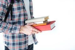 Студент держа книги изолированный на белизне с космосом экземпляра Стоковое Изображение