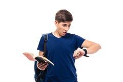 Студент держа книгу и смотря на вахте Стоковая Фотография