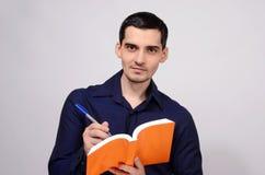 Студент держа усмехаться книги. Сочинительство учителя на тетради. стоковые изображения