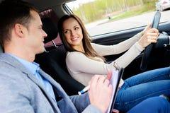 Студент инструктора по вождению и женщины в автомобиле рассмотрения Стоковые Изображения