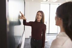 Студент и гувернер обсуждают проект на взаимодействующем Whiteboard стоковое изображение rf