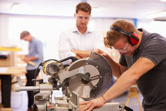 Студент и учитель в классе плотничества используя круглую пилу Стоковая Фотография