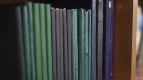 Студент колледжа вытягивая книгу с полки внутри библиотеки сток-видео