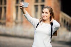 Студент колледжа девушки сидя вне здания и принимая selfie на предпосылку кампуса Стоковые Изображения