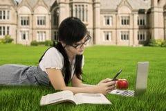 Студент колледжа отправляя СМС на поле стоковые фото