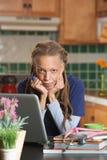 Студент-медик использует компьтер-книжку для того чтобы изучить на ее кухонном столе Стоковое фото RF
