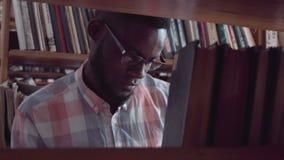 Студент молодого человека ища для книги в библиотеке сток-видео