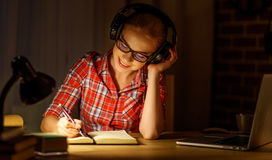 Студент молодой женщины в наушниках работая на компьютере на nig Стоковая Фотография