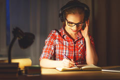 Студент молодой женщины в наушниках работая на компьютере на nig Стоковая Фотография RF