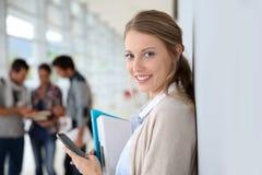 Студент молодой женщины с smartphone в прихожей Стоковые Фото