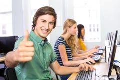 Студент показывать большие пальцы руки вверх в классе компьютера стоковое изображение rf