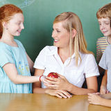 Студент принося яблоко учителя стоковая фотография rf