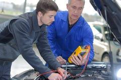 Студент при инструктор ремонтируя автомобиль во время ученичества стоковые фото