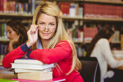 Студент при стекла чтения полагаясь на стоге книг стоковые фото
