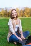 Студент сидя на зеленой траве с раскрытой тетрадью и смотреть Стоковое Изображение
