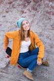 Студент сидя на скейтборде и усмехаясь на камере Стоковая Фотография
