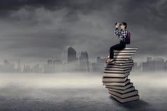 Студент смотря через бинокли над книгами Стоковая Фотография