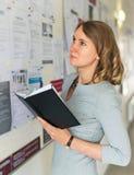 Студент смотря через предложения о работе Стоковые Изображения RF
