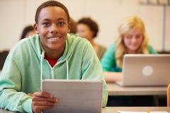 Студент средней школы на столе в классе используя таблетку цифров Стоковые Фото