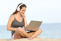 Студент уча курс с компьтер-книжкой на пляже стоковое изображение