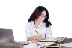 Студент читает книги литературы пока пишущ Стоковые Изображения RF