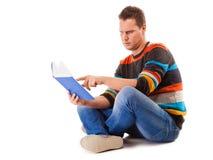 Студент читая книгу подготавливая для изолированного экзамена Стоковая Фотография