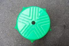 Стул зеленого цвета округленной формы пластичный на поле цемента Стоковая Фотография RF