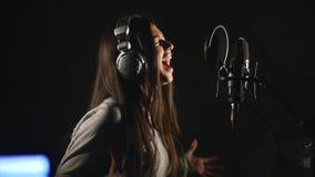 Студия аудиозаписи Женщина с наушниками и петь микрофона студии стоковое фото