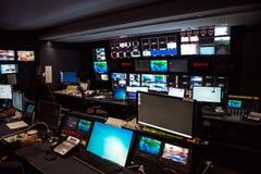 Студия новостей телевизионной передачи с много экранов компьютера и пульты управления для воздуха в реальном маштабе времени пере стоковое фото rf