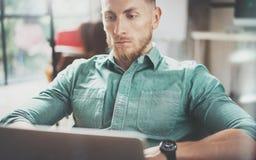 Студия просторной квартиры дизайна интерьера компьтер-книжки бородатого бизнесмена работая современная Человек сидя винтажный сту Стоковые Изображения RF