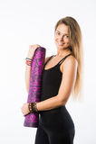 Студия сняла молодой красивой белокурой женщины держа циновку йоги и представлять готового для спортзала Стоковые Изображения