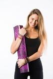 Студия сняла молодой красивой белокурой женщины держа циновку йоги и представлять готового для спортзала Стоковые Изображения RF