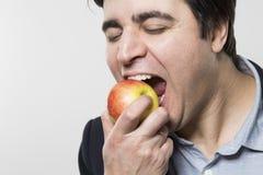 Студия сняла счастливой персоны есть яблоко Стоковое фото RF