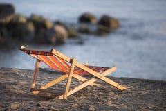 Стул на камне взгляда пляжа Стоковая Фотография