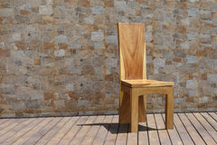Стул сделанный из твердой древесины на каменной предпосылке Стоковое Фото