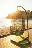 Стул уютной смертной казни через повешение отдыхая на украшать морским путем сторона на солнце вечера Стоковое фото RF