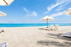 Стулья и зонтики океана бортовые с голубым небом стоковая фотография