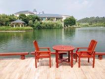 Стулья и стол около озера Стоковое Изображение