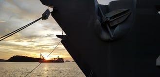 Стыковка военного корабля в гавани с с шлюпкой берега на заднем плане Стоковая Фотография