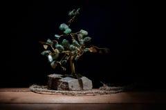 сувенир дерева и покрашенного зеленого цвета выходит камни малахита на darkbackground Стоковые Изображения
